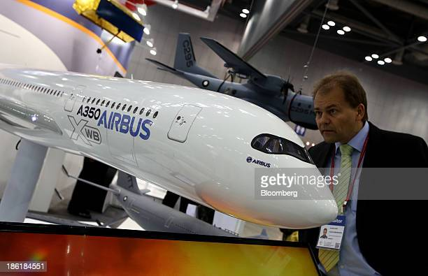 Visitor looks at a model of an Airbus SAS A350 aircraft at the Seoul International Aerospace & Defense Exhibition 2013 in Goyang, South Korea, on...