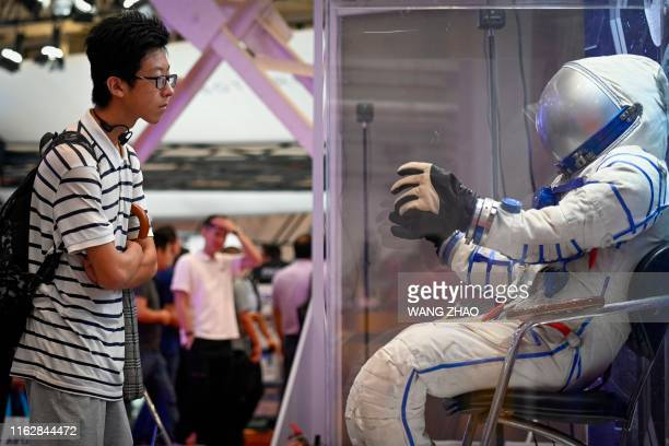 A visitor looks at a model of an astronaut at the 2019 World Robot Conference in Beijing on August 20 2019