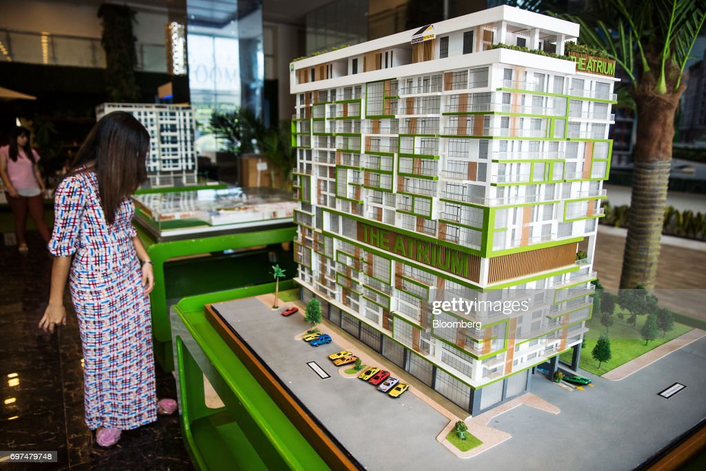 A visitor looks at a model of 'The Atrium' condominium, a residential property developed by Yadanar Myaing Construction Co., at a showroom in Yangon, Myanmar, on Monday, June 12, 2017. When the country opened to the outside world in 2011 after decades of military rule, the former British colony held promise as one of the worlds hottest tourist destinations, a last frontier for adventure travel. But it hasn't worked out that way. A construction glut has flooded Myanmar with unused hotel rooms, and poorly regulated building has damaged national treasures like the archaeological site of Bagan. Photographer: Taylor Weidman/Bloomberg via Getty Images
