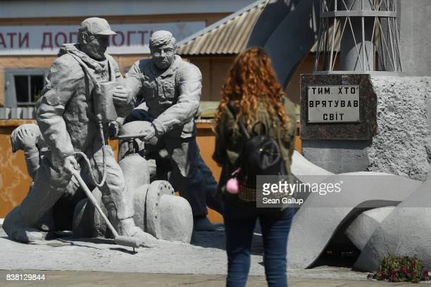 CHORNOBYL' UKRAINE AUGUST 19 A visitor looks at a monument to firefighters who responded to the 1986 reactor explosion not far from the Chernobyl...