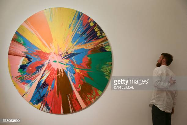 A visitor looks at a n artwork owned by the late British singer David Bowie named 'BEAUTIFUL SHATTERING SLASHING VIOLENT PINKY HACKING SPHINCTER...