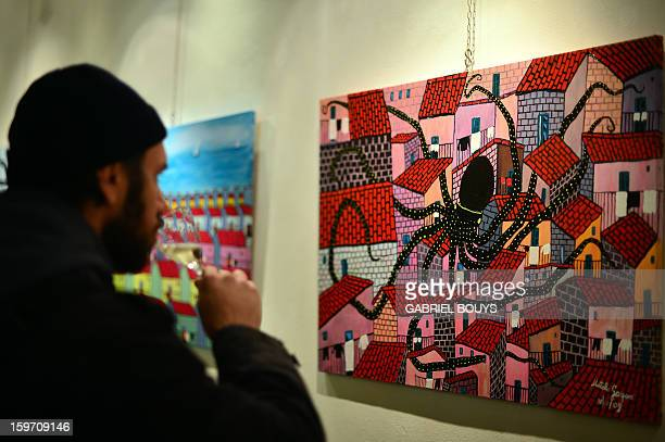 Visitor looks at a painting by Italian artist and former killer and drug trafficker for the Cosa Nostra mafia, Gaspare Mutolo, during the opening of...