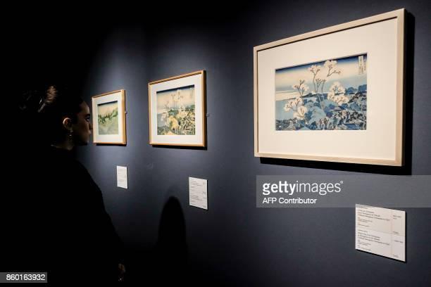 A visitor looks at a painting by Japanese artist Katsushika Hokusai ' Mount Fuji from Gotenyama at Shinagawa on the Tokaido ' during the exhibition '...