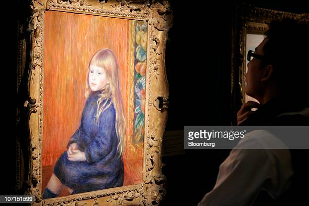 A visitor looks at a painting by Pierre Auguste Renoir entitled Enfant Assis en Robe Bleue at a Sotheby's exhibition in Hong Kong China on Friday Nov...