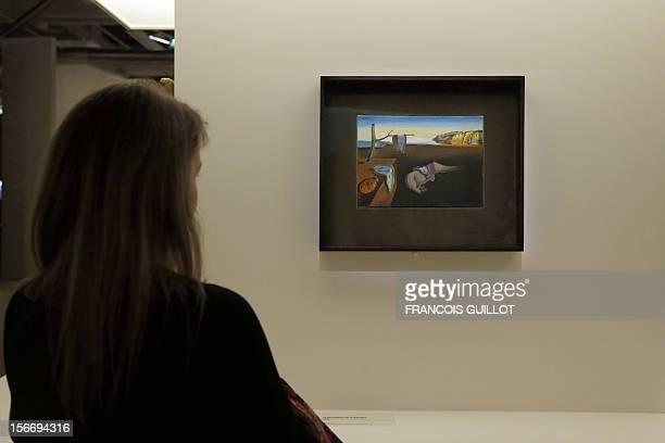 A visitor looks at a painting entitled 'La persistance de la mémoire' by Spanish surrealist artist Salvador Dali's during an exhibition devoted to...