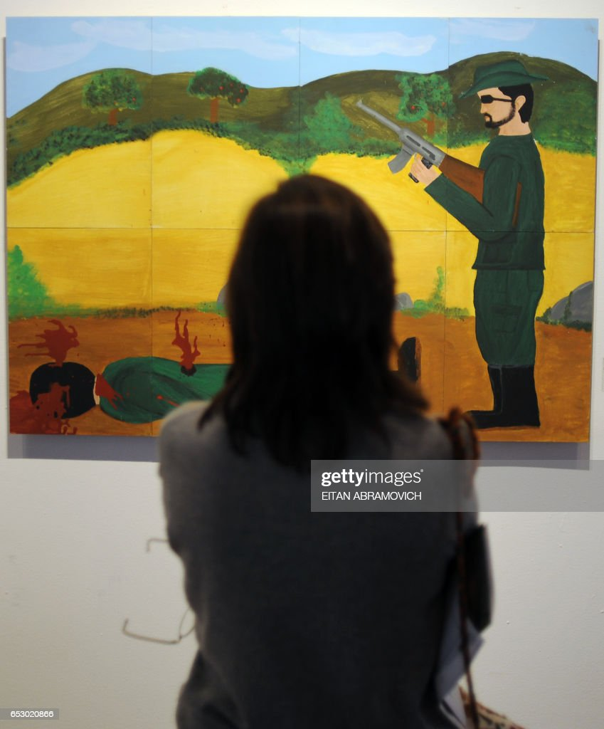 A visitor looks at a painting from the exhibit 'The War We Haven't Seen' at Bogotas Museum of Modern Arts, on October 28, 2009. The exhibit gathers 90 paintings by about 80 former combatants of Colombias four-decade-old conflict. AFP PHOTO/Eitan Abramovich /