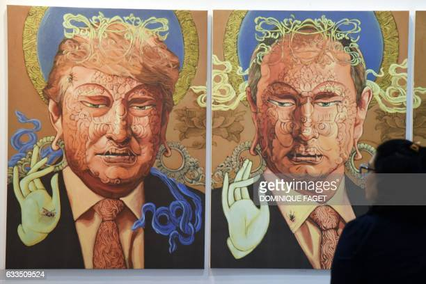 A visitor looks at a painting representing US President Donald Trump and Russian President Vladimir Putin made by Nepalese artist Sunil Sidgel at the...