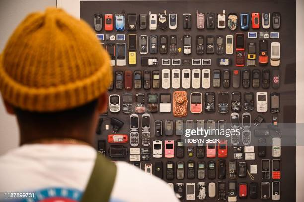 """Visitor looks at a photo of cell phones confiscated from migrants at the exhibition """"Sueno Americano / The American Dream: Photographs by Tom Kiefer""""..."""