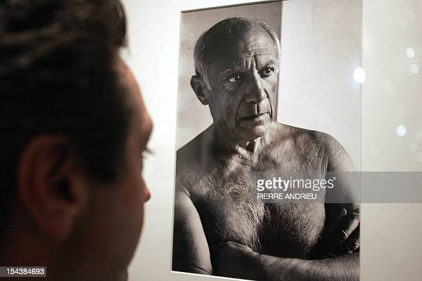 A visitor looks at a photo of Spanish painter Pablo Picasso taken by photojournalist Robert Capa who died fifty years ago 05 October 2004 at...