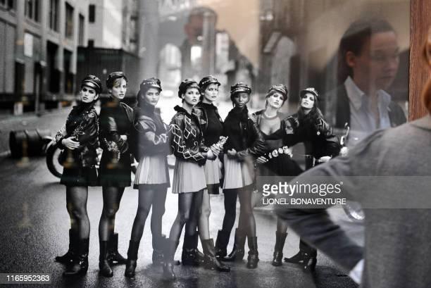 A visitor looks at a photograph of US model Cindy Crawford German model Tatjana Patitz Danish model Helena Christensen Canadian model Linda...