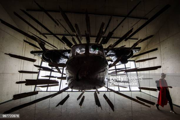 TOPSHOT A visitor looks at a plane used in the alpine chase sequence in the 007 movie 'Spectre' which is displayed at the James Bond cinematic...