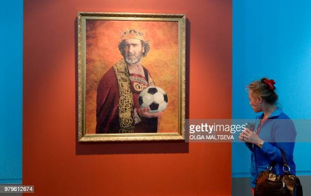 A visitor looks at a portrait of French football legend Eric Cantona as she attends the Art Project 'Like the Gods' presented by the Museum of the...
