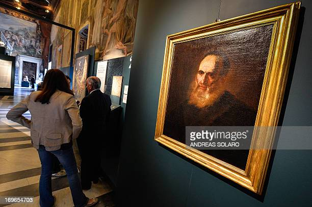 A visitor looks at a portrait of Greek scientist Archimedes during the 'Archimedes art and science of the inventor' exhibition on May 30 at the...