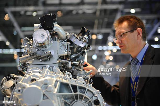 A visitor looks at a Renault TCe 130 motor on display on the second press day of the Geneva International Motor Show in Geneva Switzerland on...