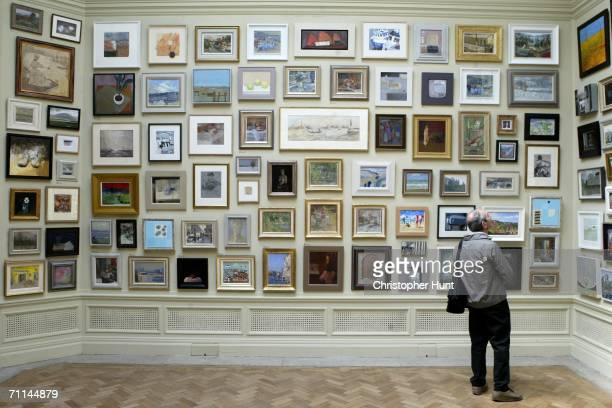 A visitor looks at a selection of paintings at the press view for the Royal Academy Summer Exhibition 2006 the world's largest open contemporary art...