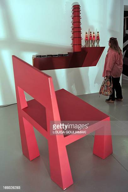 A visitor looks at a 'shelve' by Hain Steinback next to a chair by Alessandro Mendini arranged by architect Andreas Angelidakis from the collections...