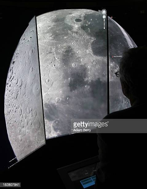 A visitor looks at a threedimensional rendering of the moon while using Google Earth software on September 26 2012 at the official opening party of...