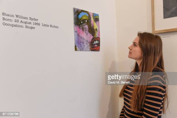 A visitor looks at a work by artist Jeremy Deller entitled 'Hallelujah Shaun Ryder's Family Tree' during a press preview of 'North Fashioning...