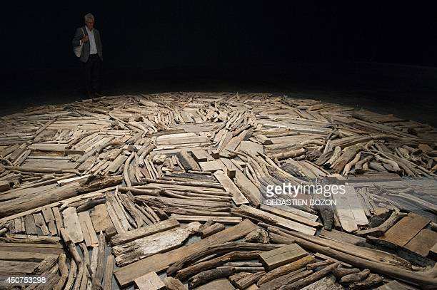 A visitor looks at a work of art by British sculptor photographer and painter Richard Long called 'River Avon Driftwood' on June 17 2014 during the...