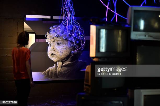 """Visitor looks at a work of art by Nasti entitled """"lecture de pensee"""" during a street art exhibition in a former German WWII submarine base in..."""
