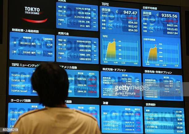 A visitor looks at an electoric board displaying the Nikkei Index and other figures at Tokyo Stock Exchange on October 14 2008 in Tokyo Japan Nikkei...