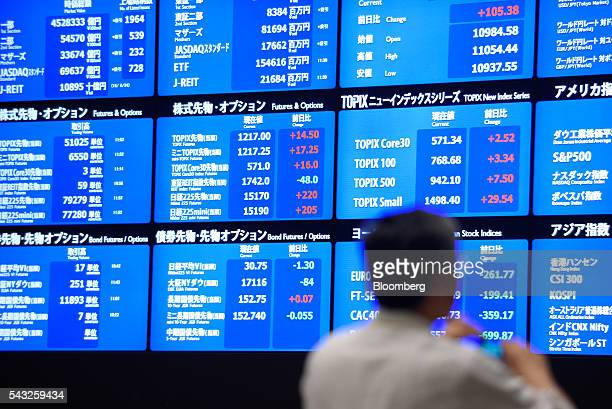 A visitor looks at an electronic board displaying market indices at the Tokyo Stock Exchange operated by Japan Exchange Group Inc in Tokyo Japan on...