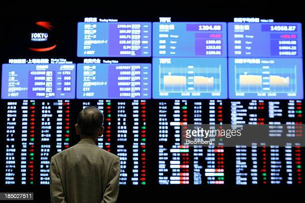 A visitor looks at an electronic board displaying stock figures at the Tokyo Stock Exchange in Tokyo Japan on Thursday Oct 17 2013 Japanese shares...