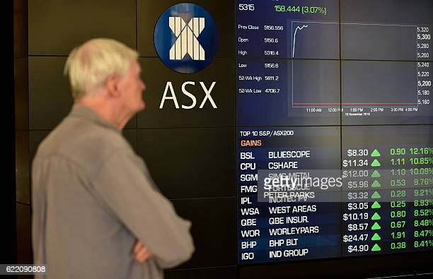 A visitor looks at an electronic display at the Australian Securities Exchange showing stocks gains during opening trading in Sydney on November 10...