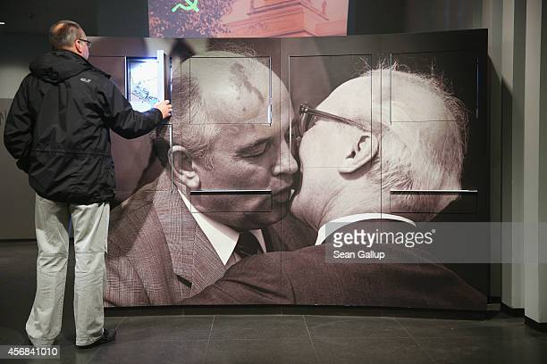 A visitor looks at an exhibit next to a photograph of former Soviet leader Mikhail Gorbachev embracing former East German communist leader Erich...