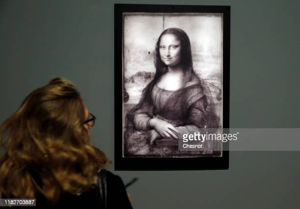 A visitor looks at an infrared reflectography of the painting 'Mona Lisa' by the Italian Renaissance artist Leonardo da Vinci during a press visit of...