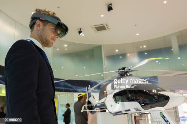 A visitor looks at an interactive augmented reality scale model of the Airbus H160 helicopter in the company's hospitality chalet at the Farnborough...