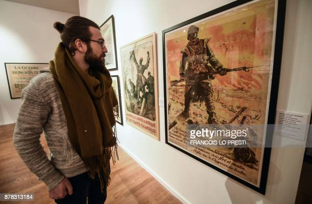 A visitor looks at an old poster displayed in an exhibition on the centenary of the battle of Cambrai on November 24 2017 in Cambrai museum / AFP...