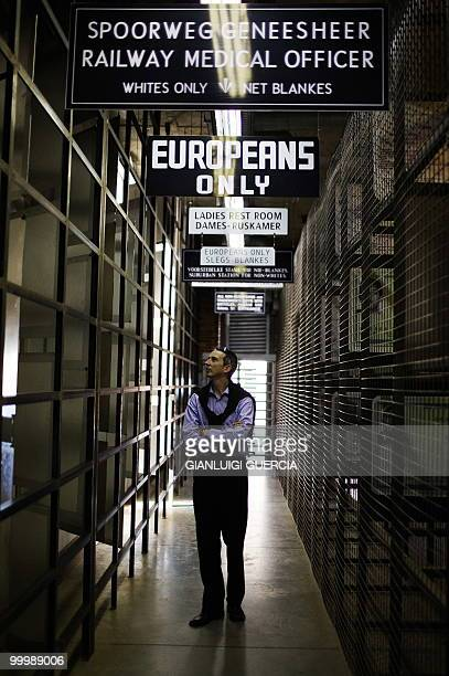 A visitor looks at apartheid era identity cards on May 19 2010 at the Apartheid museum in Johannesburg South Africa The Apartheid Museum opened in...