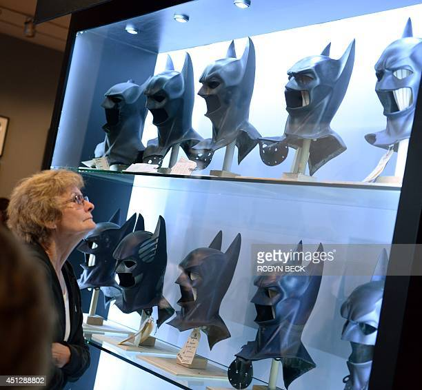 A visitor looks at Batman masks used in the seven Batman films at The Batman Exhibit on the exhibitions opening day on the Warner Bros VIP Studio...