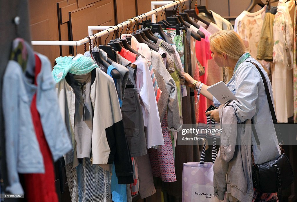 A visitor looks at clothing by the brand Sylvian Heach on display at the Bread and Butter trade show at the former Tempelhof airport during Mercedes-Benz Fashion Week in Berlin on July 3, 2013 in Berlin, Germany.