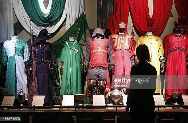 A visitor looks at costumes during an exhibition on the literary characters and themes of the Harry Potter novels at the Cite Du Cinema on April 2 in...
