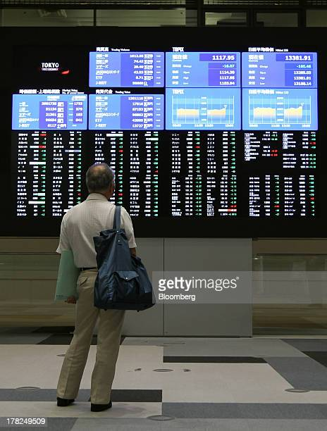 Visitor looks at electronic boards displaying stock figures at the Tokyo Stock Exchange in Tokyo, Japan, on Wednesday, Aug. 28, 2013. Japanese shares...
