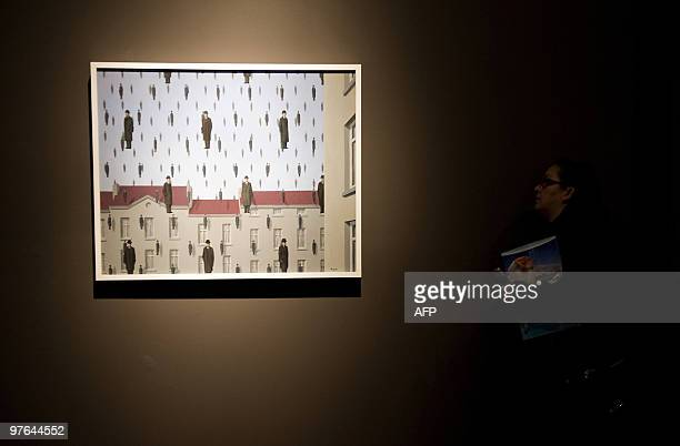 A visitor looks at 'Golconda 1953' by the Belgian artiste Rene Magritte exhibited during a press conference at the Fine Arts Palace in Mexico City on...