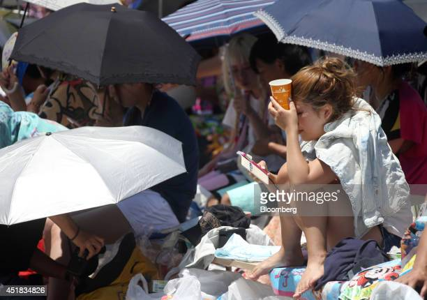 A visitor looks at her smartphone while waiting for a show at Tokyo Disneyland operated by Oriental Land Co in Urayasu Chiba Prefecture Japan on...