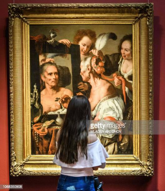 A visitor looks at Italian painter Bernardo Strozzi's 'Vanitas' at the Pushkin State Museum of Fine Arts in Moscow on December 4 2018 / RESTRICTED TO...