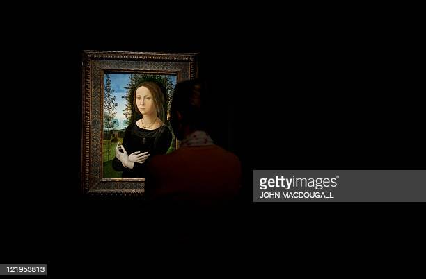 A visitor looks at Italian painter Lorenzo di Credi's 'Portrait of a Young Woman' during a press preview of the exhibition 'Renaissance Faces...