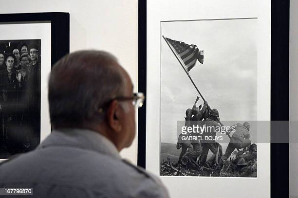 A visitor looks at Joe Rosenthal's Raising the Flag on Iwo Jima 1945 during the 'Life I grandi fotografi exhibition at the auditorium on April 30...