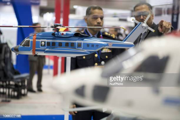 A visitor looks at Lockheed Martin Industries' helicopter model during Japan Aerospace 2018 air show in Tokyo Japan November 28 2018