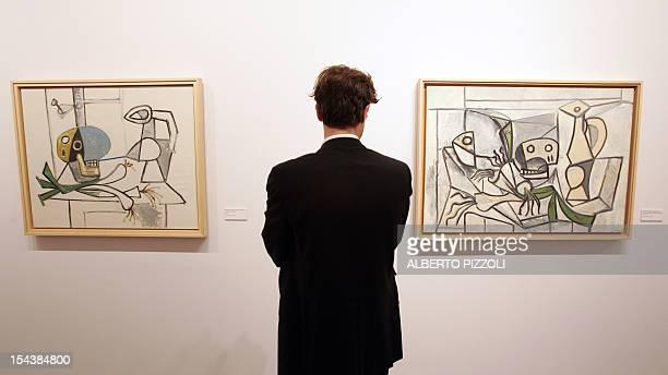 A visitor looks at 'Nature morte a la tete de mort cruche poireaux' and 'Nature morte aux poireaux tete de poisson crane et pichet' by painter Pablo...