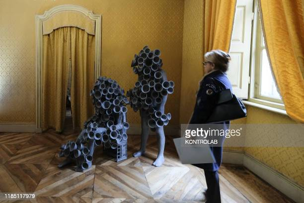 A visitor looks at one of the artworks by Italian sculptor Paolo Grassino which is displayed at the exibition T30 at Palazzo Saluzzo Paesana