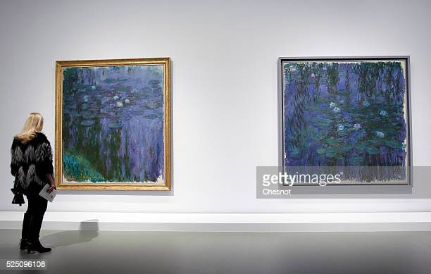 A visitor looks at paintings Blue water lilies and Water lilies of Claude Monet as part of the opening of the exhibition Keys to a Passion at the...
