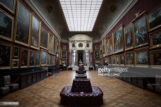 Visitor looks at paintings of the Chateau of Chantilly art collection on March 2 at the Chateau de Chantilly in Chantilly, northern France. -...