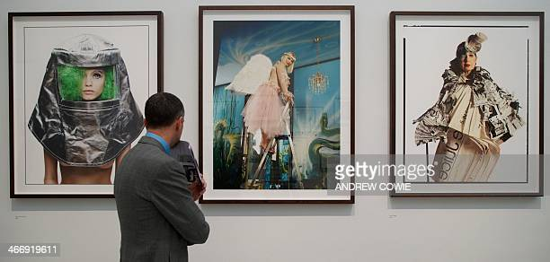 A visitor looks at photographs by British photographer David Bailey of Abby Lee Kershaw Cicciolina and Anna Piaggi at an exhibition of his works...