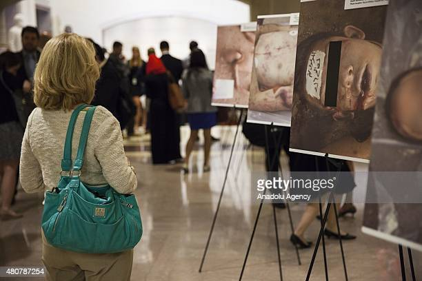 A visitor looks at photographs in the 'Caesar's Photos Inside Syria's Secret Prisons' a collection of photographs smuggled out of Syria documenting...