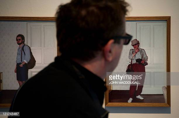 A visitor looks at photographs showing examples of disguises used by members of the former east German secret police at German artist Simon Menner's...